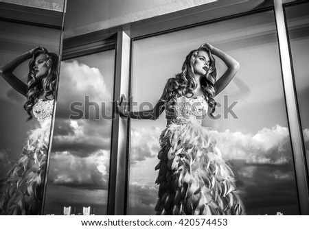 Young sensual & beauty woman in fashionable dress pose indoor. Black-white fashion portrait.