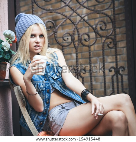 Young sensual blonde girl sitting outdoor on the street while smoking sigarette with cup of hot coffee espresso. Outdoors, lifestyle. - stock photo