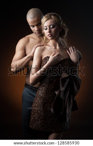 young sensual caucasian woman in dress made of coffee beans and black man standing over gradient orange background - stock photo