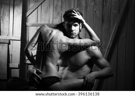 Young sensual couple of muscular macho man with bare torso and pretty sexy topless woman with back sitting on lover indoor on wooden background black and white, horizontal picture - stock photo