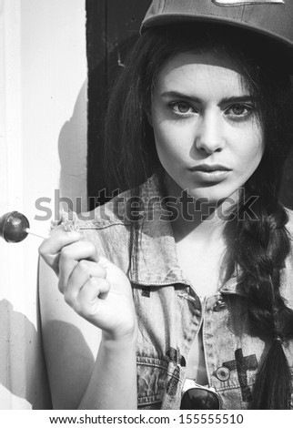 Young sensual girl sucking lollipop. Black and white color. - stock photo