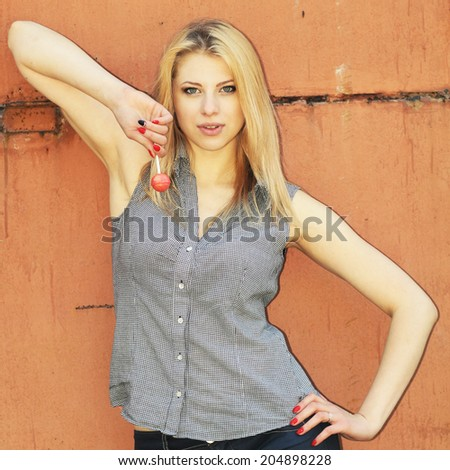 Young sensual girl sucking lollipop on the background of rusty iron wall. Outdoors, lifestyle. - stock photo