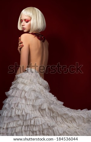 Young sensual woman in white skirt over red background - stock photo