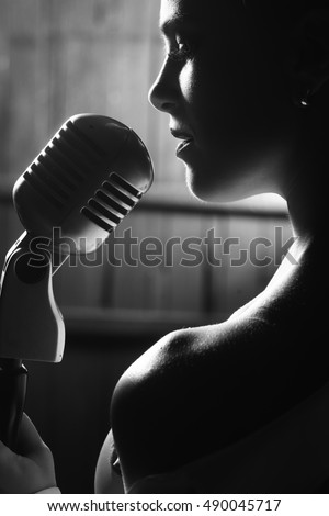 young sensual woman sexy silhouette profile with pretty face and bare shoulder near studio silver microphone on wooden background, closeup