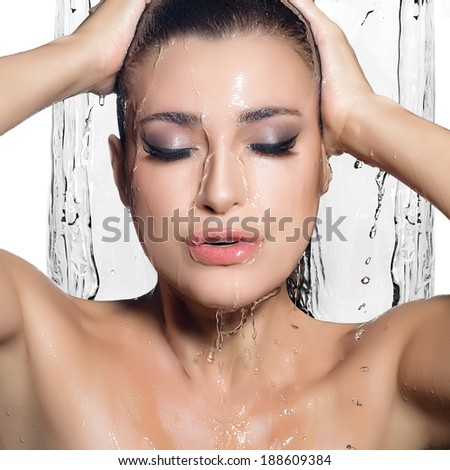 Young sensuality woman under stream of water enjoying the shower. Wet makeup. Beauty and Fashion - stock photo