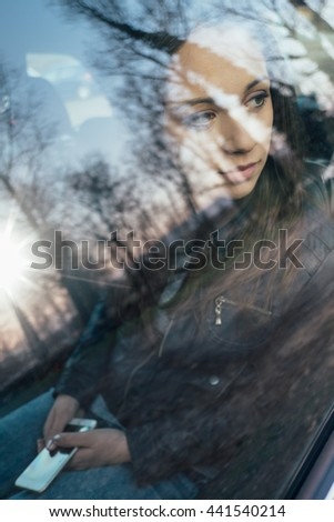 Young serene woman sitting in the backseat of a car and looking away, trees reflecting on the car window glass, travel concept - stock photo