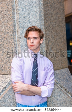 Young serious American businessman in New York. Wearing light pink shirt, black, white polkadot necktie, a college student standing by column outside, crossing arms, thinking. Photo stylized look.  - stock photo