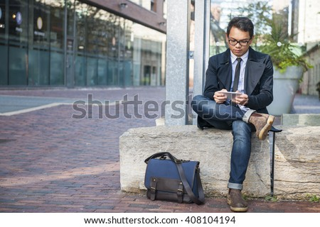 Young serious asian business man looking at mobile phone sitting outside on city street with copy space