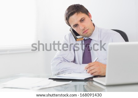 Young serious businessman using mobile phone and laptop while writing in diary at office - stock photo