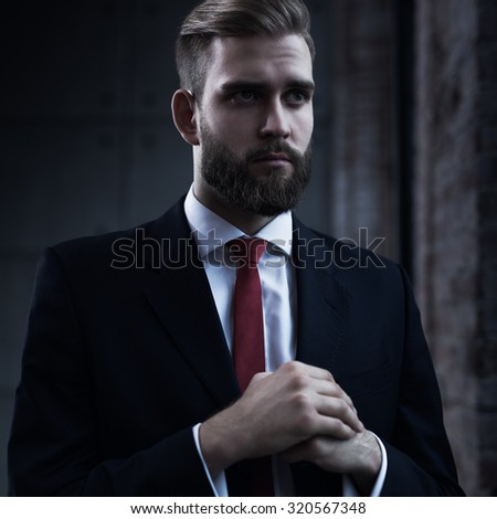 Young serious businessman with beard in black suit portrait. - stock photo