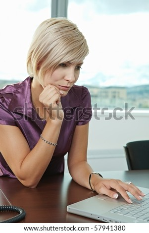 Young serious businesswoman sitting at table in office meeting room, working with laptop computer, thinking. - stock photo