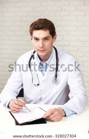 Young serious doctor sitting in medical office with folder