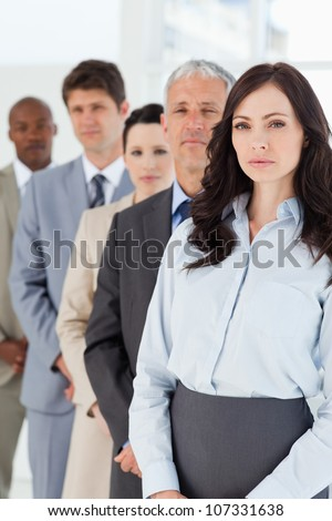 Young serious executive woman standing upright in front of her co-workers