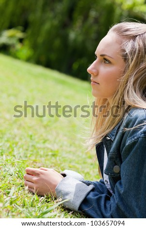 Young serious girl looking ahead while lying on the grass in the countryside