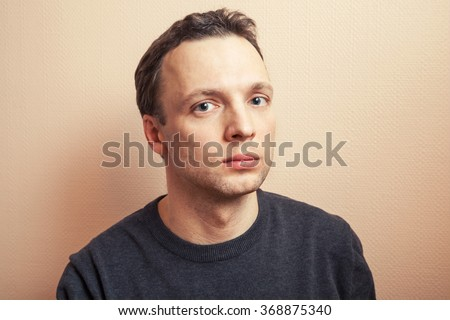 Young serious handsome Caucasian man studio portrait over gray wall background - stock photo
