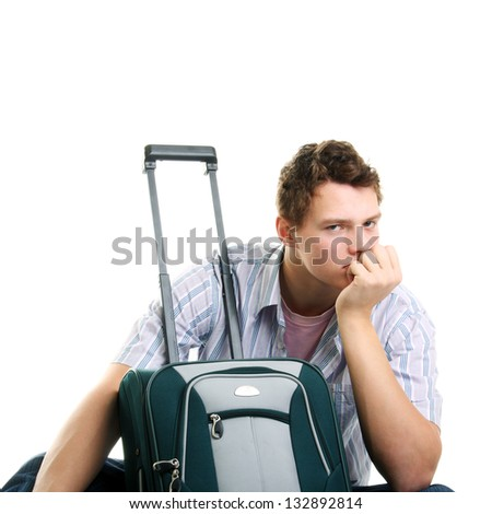 young serious handsome man near the suitcase - stock photo