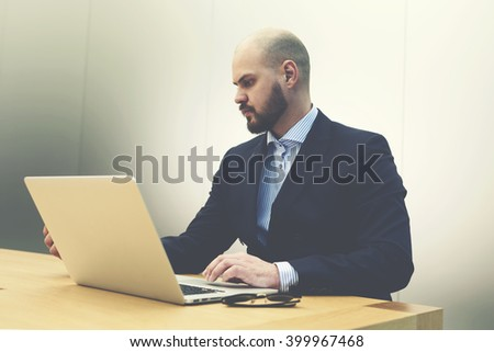 Young serious man investor is examining on laptop computer activity of company which he wants to invest. Male skilled employer is reading on portable net-book resume before interview with specialists - stock photo