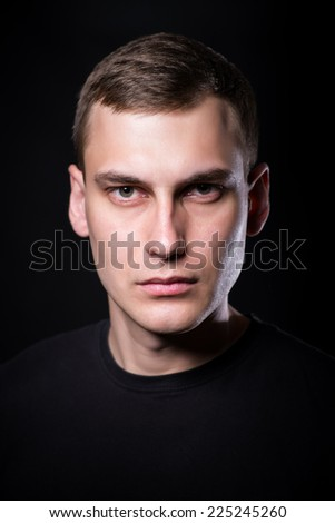 Young serious man on black background in low key