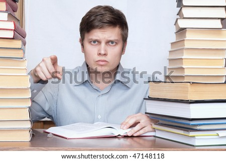 Young serious man show finger to you between books