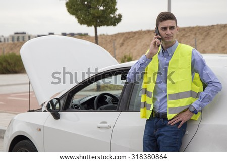 Young serious man wearing reflective vest, talking on his cell phone next to his damaged car with the hood open