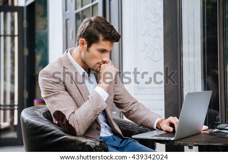 Young serious successful businessman working on a laptop while sitting in cafe - stock photo