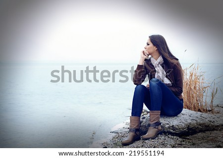 Young serious woman near river - stock photo