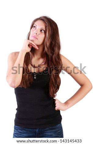 Young serious woman props up chin and looks away isolated on white background.