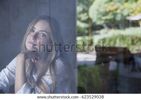 young serious woman sitting in cafe through window glass from outside with copy space