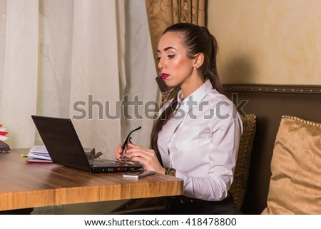 Young serious woman working with laptop computer in cafe