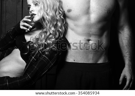 Young sexual attractive sensual couple of blonde woman with long curly hair and naked muscular man with beautiful body close to each other in studio black and white, horizontal picture - stock photo