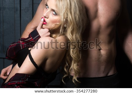 Young sexual attractive sensual couple of blonde woman with long curly hair and naked muscular man with beautiful body close to each other in studio on wooden background, horizontal picture - stock photo