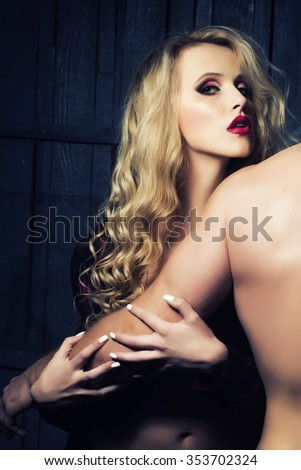 Young sexual attractive sensual couple of blonde woman with long curly hair embracing naked muscular man with beautiful body close to each other in studio on wooden background, vertical picture - stock photo