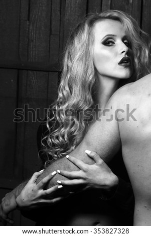 Young sexual attractive sensual couple of blonde woman with long curly hair embracing naked muscular man with beautiful body close to each other in studio black and white, vertical picture - stock photo