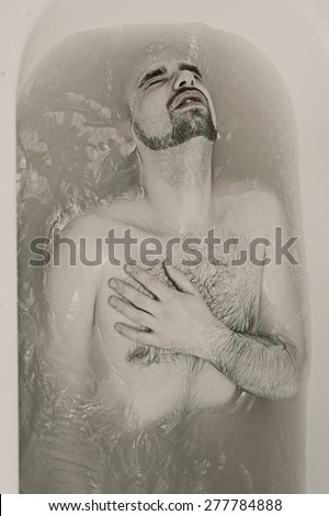 young sexual naked guy in bath close up - stock photo