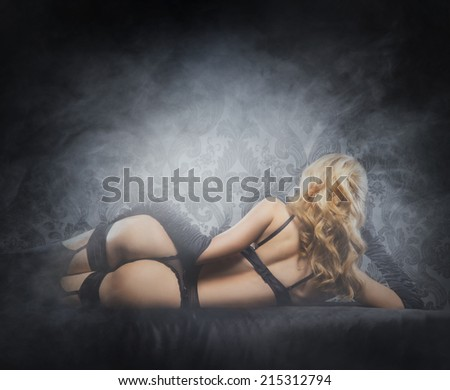 Young, sexy and beautiful blond girl in erotic lingerie over smoky background - stock photo