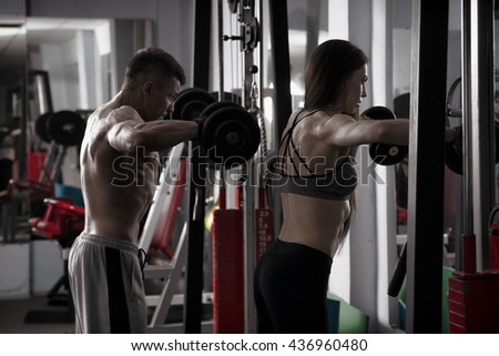 Young sexy athletic man and woman workout with dumbbells in gym. Perfect muscular body - stock photo