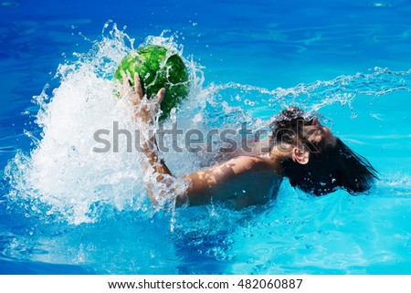 young sexy bearded man with wet hair and beard swimming in pool with blue water and drops holds green watermelon sunny summer day outdoor