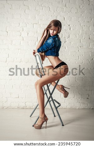 Young sexy beautiful blonde woman posing on chair. vogue style fashion portrait. - stock photo