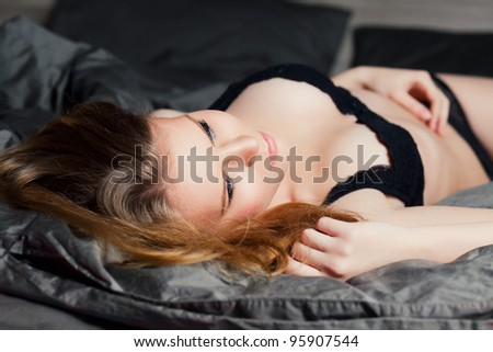 Young sexy beautiful woman laying in underwear - stock photo