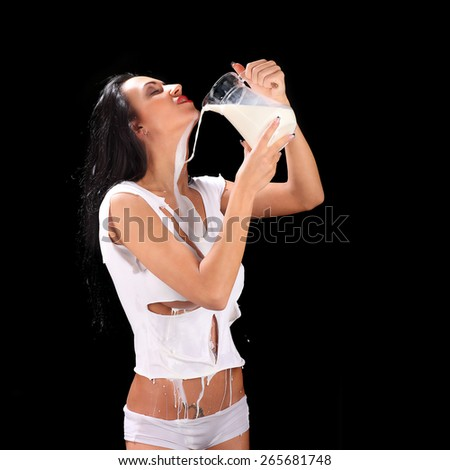 Young sexy beautiful woman with milk, isolated on black studio - stock photo