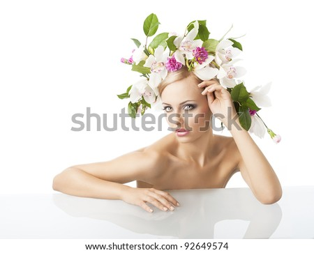 young sexy beautiful woman with naked shoulder and wearing a big crown of flower and leaves as spring queen, she is behind the table,  her face is turned of three quarters, she looks in to the lens - stock photo