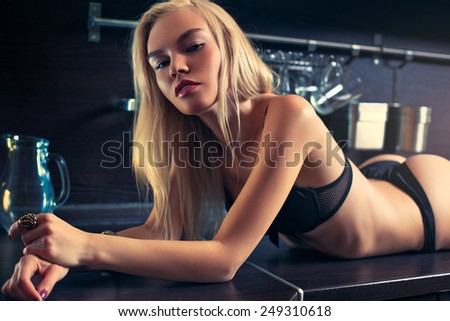 Young sexy blond woman in black lingerie lying on kitchen table portrait. - stock photo