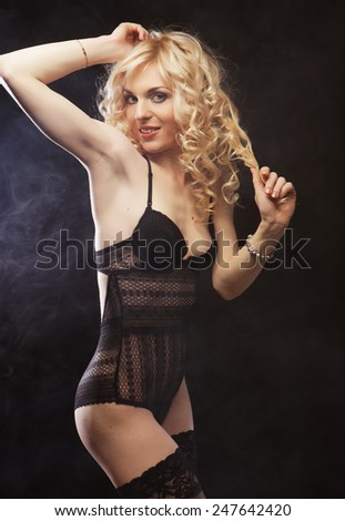 young sexy blond woman in  lingerie over dark background - stock photo