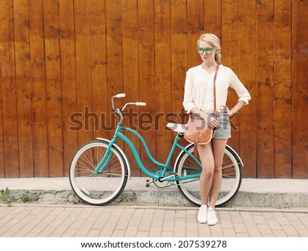 Young sexy blonde girl is standing near the vintage green bicycle with brown vintage bag in green sunglasses. - stock photo