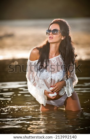Young sexy brunette girl in wet white blouse posing provocatively in water. Sensual attractive woman with black sunglasses, summer shot. Long hair female with perfect body at beach in sunny day. - stock photo