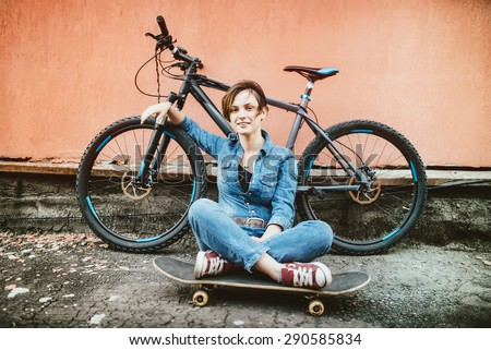 Young sexy brunette girl with short hair standing near vintage bicycle and holding a skateboard, having fun and a good mood while looking in camera and smiling