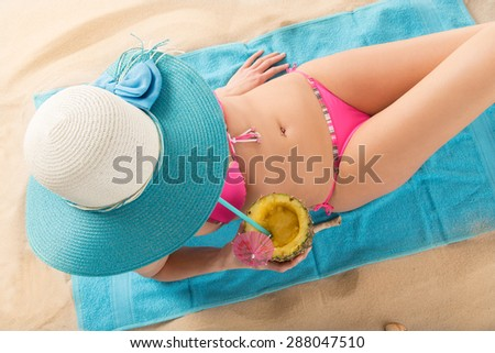 Young sexy brunette in pink swimsuit on tropical beach. - stock photo