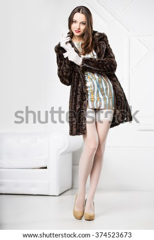 Young sexy brunette posing in frank dress, white stockings and fur coat