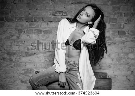 Young sexy brunette wearing bra, shirt and jeans. Monochrome - stock photo