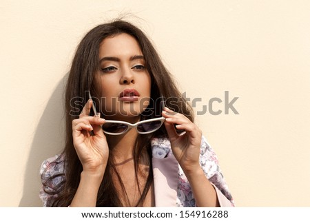 Young sexy brunette woman closeup portrait. Stylish woman posing on the street with interested look and sunglasses in her hands. - stock photo